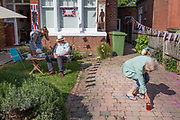 As the Coronavirus lockdown continues over the May Bank Holiday, the nation commemorates the 75th anniversary of VE Day (Victory in Europe Day, the day that Germany officially surrendered in 1945) and in Dulwich, neighbours and residents emerge from their homes to party while still observing social distancing rules. Home-owners have afternoon tea while distancing themselves by leaving a mug of tea for a neighbour to collect on the ground, on 8th May 2020, in London, England.