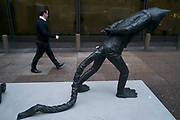 People passing a pacing cat creature sculpture in the City of London, England, UK. The city has a long tradition of having modern sculptures on show thanks to the Sculpture in the City initiative, which selects contemporary art pieces in and around the Square Mile.