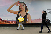 A woman shopper yawns as she walks past a billboard ad featuring the face of a model advertising a perfume outside the retailer Debenhams on Oxford Street, on 16th April 2018, in London, England.