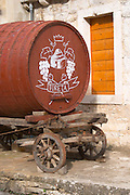 An old wooden cart with a big barrel for transporting wine used as a promotional sign outside the winery. Toreta Vinarija Winery in Smokvica village on Korcula island. Vinarija Toreta Winery, Smokvica town. Peljesac peninsula. Dalmatian Coast, Croatia, Europe.