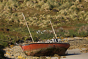 The Redwing (blown aground) in West Point Harbour. This boat belonged to one of the FIGAS pilots who was killed in a plane crash. It now lies here in his memory.<br /> West Point Island. Off of West Falkland. FALKLAND ISLANDS.<br /> An island owned by Roddy and Lily Napier who have lived there for most of their lives. It is a small sheep farm with about 1,000 sheep and some cattle but now they survive mainly on tourism with several cruise ships visiting during the summer. The island is renowed for its huge Black-browed Albatross Rockhopper Penguin colonies.