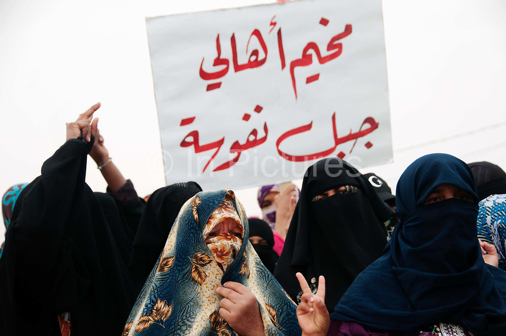 Tunisia 2011. Remada camp for refugees from Libya. After Friday prayers refugees (mostly mothers and children) held a demonstration around the camp. One of the chants was 'We don't want milk for our children we want guns for our fighters'. Women show victory fingers.