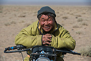 Gobi nomad on motorbike<br /> Herding animals with motorbike<br /> Gobi Desert<br /> Mongolia
