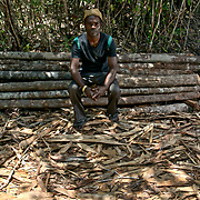Tovolah Michael Cyrille, chief of Andranokoditra village, pauses in the forest sitting on felled trees cut illegally by loggers. Madagascar