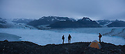 Photographer James Balog (r) and Adam LeWinter (l), of the Extreme Ice Survey, and University of Colorado glaciologist Tad Pfeffer stand around camp at twilight looking out over the terminus of the Columbia Glacier, near Valdez, Alaska.