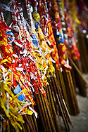 Incense sticks wrapped in red, blue and yellow papers and aligned n a row