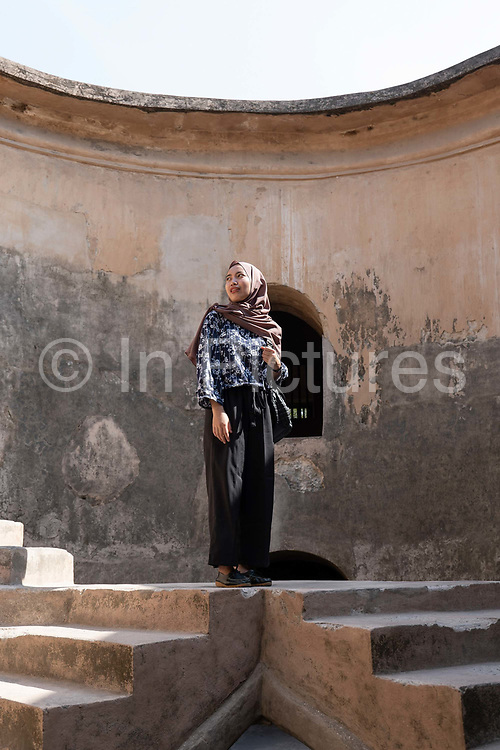 A muslim lady wearing a hijab stands on an elevated platform at the Sumur Gumuling, also known as the Gumuling Well, within the Taman Sari Water Castle complex on the 23rd October 2019 in Yogyakarta in Indonesia. The Sumur Gumuling is a round building that was functioned as a mosque at the time of Yogyakarta Palace. The Taman Sari Water Castle is a historic bathing complex in Yogyakarta.