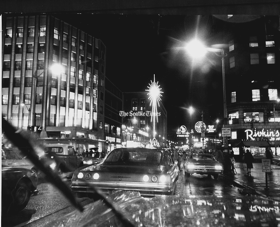 Looking north on Fourth Avenue in downtown Seattle, lights from automobiles glistened and winked as Christmas shoppers hurried on their appointed rounds. Street lights blinked and the emblem of a department store shone like a huge decoration. This photo was taken from the window of an automobile.<br />