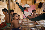 30 JUNE 2006 - PHNOM PENH, CAMBODIA: Workers in a brick factory in Phnom Penh, Cambodia, relax in the hut that is their home on the grounds of the facotry. According the United Nations Food and Agricultural Organization, there are more than 70 brick factories in Phnom Penh and its environs. Environmentalists are concerned that the factories, most of which burn wood in their kilns, contribute to deforestation in Cambodia. They are encouraging factory owners to switch to burning rice husks, as brick kilns in neighboring Vietnam do. The brick factories are kept busy feeding Phnom Penh's nearly insatiable appetite for building materials as the city is in the midst of a building boom brought by on economic development and the need for new office complexes and tourist hotels.  PHOTO BY JACK KURTZ