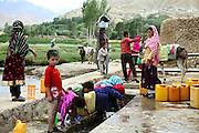 Villagers are collecting water and washing clothes next to a small river in Bamyan, Afghanistan. In the town there is no electricity or running water. Power is only being provided by generators or solar panels. The Buddhas of Bamiyan were two 6th century monumental statues of standing Buddhas carved into the side of a cliff in the Bamiyan valley in the Hazarajat region of central Afghanistan, situated 230 km northwest of Kabul at an altitude of 2500 meters. The statues represented the classic blended style of Gandhara art. The main bodies were hewn directly from the sandstone cliffs, but details were modelled in mud mixed with straw, coated with stucco. Amid widespread international condemnation, the smaller statues (55 and 39 meters respectively) were intentionally dynamited and destroyed in 2001 by the Taliban because they believed them to be un-Islamic idols. Once a stopping point along the Silk Road between China and the Middle East, researchers think Bamiyan was the site of monasteries housing as many as 5,000 monks during its peak as a Buddhist centre in the 6th and 7th centuries. It is now a UNESCO Heritage Site since 2003. Archaeologists from various countries across the world have been engaged in preservation, general maintenance around the site and renovation. Professor Tarzi, a notable An Afghan-born archaeologist from France, and a teacher in Strasbourg University, has been searching for a legendary 300m Sleeping Buddha statue in various sites between the original standing ones, as documented in the old account of a renowned Chinese scholar, Xuanzang, visiting the area in the 7th century. Professor Tarzi worked on projects to restore the other Bamiyan Buddhas in the late 1970s and has spent most of his career researching the existence of the missing giant Buddha in the valley.