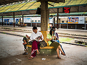 26 OCTOBER 2015 - YANGON, MYANMAR:  Burmese wait to catch a Yangon Circular Train. The Yangon Circular Railway is the local commuter rail network that serves the Yangon metropolitan area. Operated by Myanmar Railways, the 45.9-kilometre (28.5mi) 39-station loop system connects satellite towns and suburban areas to the city. The railway has about 200 coaches, runs 20 times daily and sells 100,000 to 150,000 tickets daily. The loop, which takes about three hours to complete, is a popular for tourists to see a cross section of life in Yangon. The trains run from 3:45 am to 10:15 pm daily. The cost of a ticket for a distance of 15 miles is ten kyats (~nine US cents), and for over 15 miles is twenty kyats (~18 US cents).    PHOTO BY JACK KURTZ