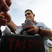 A man in a Mitt Romney mask plays out a skit during a protest march in a parade during the Republican National Convention in Tampa, Fla. on Wednesday, August 29, 2012. (AP Photo/Alex Menendez)