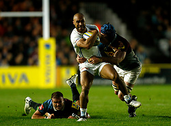 Exeter's Olly Woodburn (centre) is tackled by Harlequins' James Horwill and Jamie Roberts during the Aviva Premiership match at Twickenham Stoop, London.