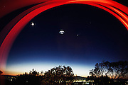 Roswell UFO story (1947 UFO incident). UFO's over Napa, California seen by Peter Menzel and Faith D'Aluisio. The center object is actually a kitchen steamer basket thrown in the air and lit with a flash. Also seen are the moon and a comet. The red streaks are made by a flashlight. (1997)