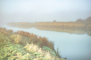 Rural landscape with the river Arun early morning in England with fog and still water