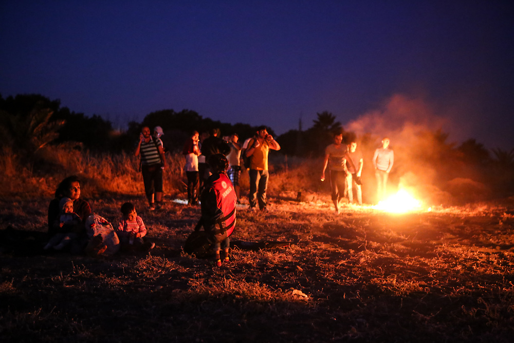 Syrian refugees wait on the shore of Kos, Greece while they burn plastic life jackets as a signal fire for authorities to arrive at their location on the dawn of July 6, 2015. Two boats carrying about 30 Syrian refugees in total landed on a portion of the island's shore that is not easily accessible.