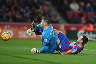 Jack Butland, the Stoke city goalkeeper bravely stops James McArthur of Crystal Palace . Barclays Premier league match, Stoke city v Crystal Palace at the Britannia Stadium in Stoke on Trent, Staffs on Saturday 19th December 2015.<br /> pic by Andrew Orchard, Andrew Orchard sports photography.