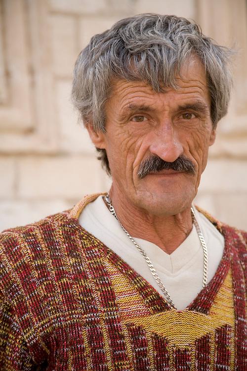 Europe, Croatia, Dalmatia, Dubrovnik.  Old man in front of stone wall.