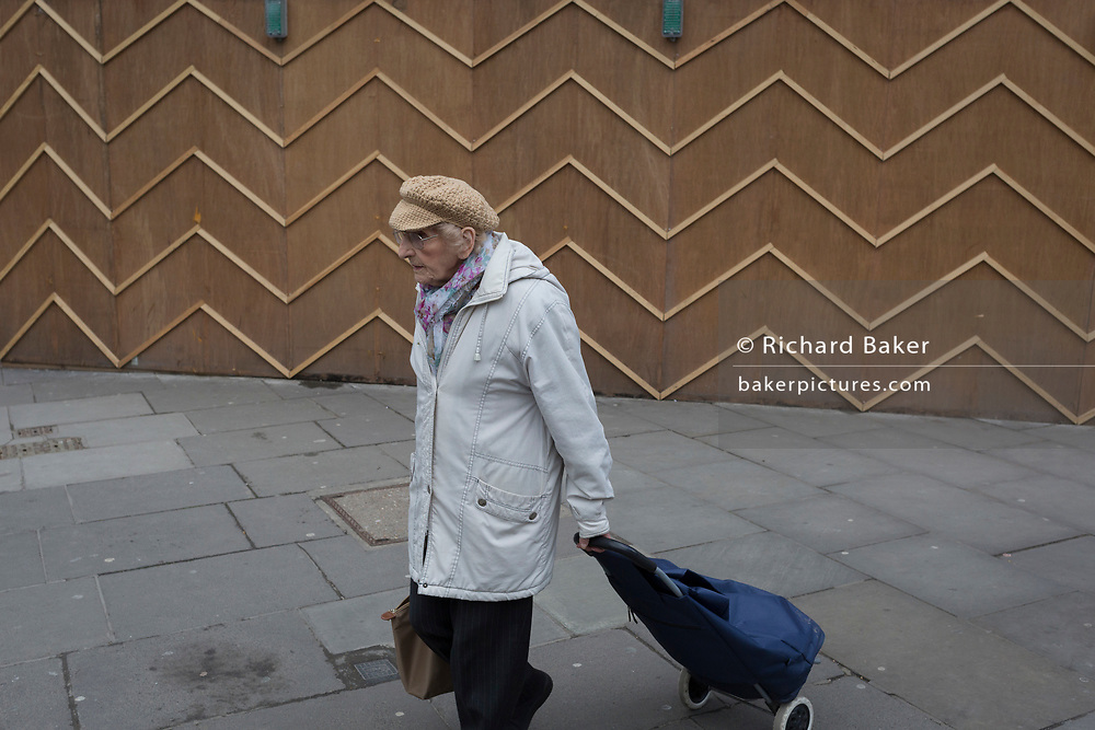 An elderly pensioner walks past the zigzag battens of a construction hoarding at Notting Hill, on 13th March 2018, in London, England.
