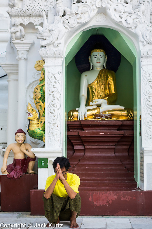 15 JUNE 2013 - YANGON, MYANMAR: A man prays at Shwedagon Pagoda. The Shwedagon Pagoda is officially known as Shwedagon Zedi Daw and is also called the Great Dagon Pagoda or the Golden Pagoda. It is a 99 metres (325ft) tall pagoda and stupa located in Yangon, Burma. The pagoda lies to the west of on Singuttara Hill, and dominates the skyline of the city. It is the most sacred Buddhist pagoda in Myanmar and contains relics of the past four Buddhas enshrined: the staff of Kakusandha, the water filter of Koṇāgamana, a piece of the robe of Kassapa and eight strands of hair fromGautama, the historical Buddha. The pagoda was built between the 6th and 10th centuries by the Mon people, who used to dominate the area around what is now Yangon (Rangoon). The pagoda has been renovated numerous times through the centuries. Millions of Burmese and tens of thousands of tourists visit the pagoda every year, which is the most visited site in Yangon.  PHOTO BY JACK KURTZ