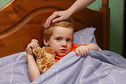 Single parent's hand placed on son's head as he lies in bed with his teddy bear,