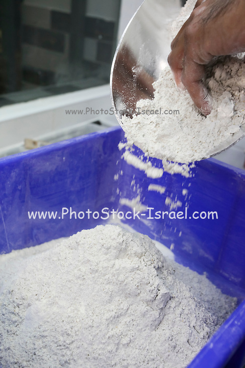 Bakers adds flour to a dogh batter
