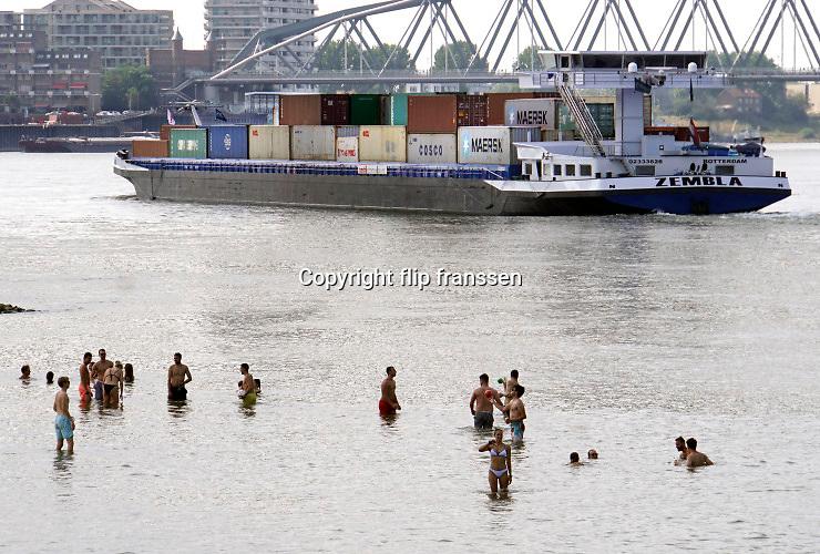 Nederland, nijmegen, 12-8-2020 Vooral jonge mensen zoeken verkoeling aan de oevers van de waal op deze tropisch warme zomerdag . Het is eigenlijk verboden in de rivier te zwemmen vanwege de stroming en het drukke scheepvaartverkeer . Deze strandje liggen tussen de kribben in de Stadswaard . Foto: ANP/ Hollandse Hoogte/ Flip Franssen