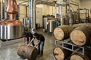 Vishal Gauri and Virag Saksena (right) roll a whiskey barrel at 10th Street Distillery in San Jose, California, on September 4, 2019. (Stan Olszewski for Content Magazine)