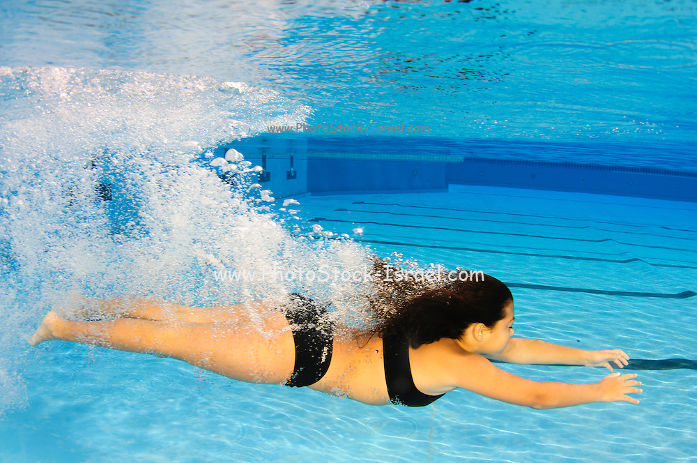 A 12 year old female teen free diving underwater in a swimming pool