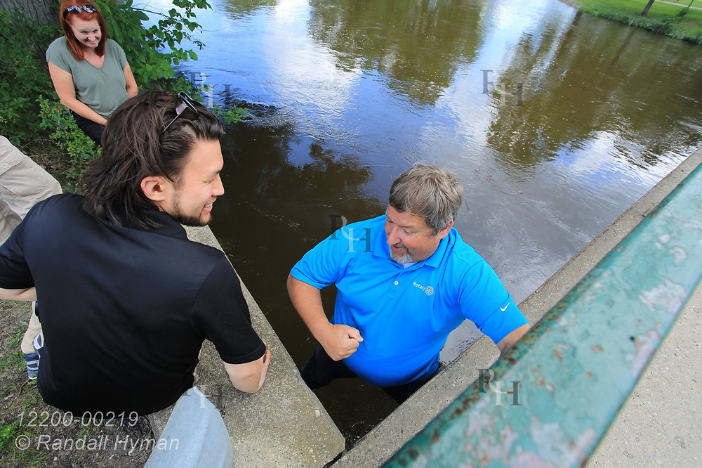 Hyfi CEO Brandon Wong listens to City Manager Joe Sawyer, who perches on bridge abutment over floodwaters of Shiawassee River before installation of water-level sensor; Corunna, Michigan.