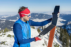 Man holding skis on mountain against sky