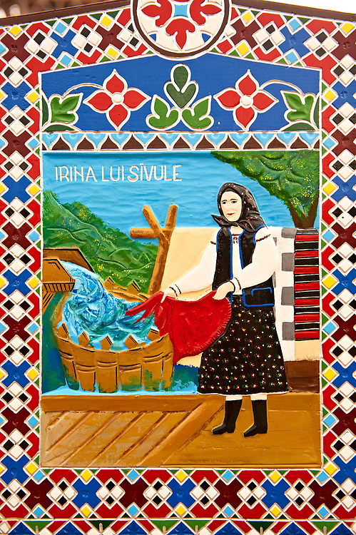 Tombstone of a washer women,  The  Merry Cemetery ( Cimitirul Vesel ),  Săpânţa, Maramares, Northern Transylvania, Romania.  The naive folk art style of the tombstones created by woodcarver  Stan Ioan Pătraş (1909 - 1977) who created in his lifetime over 700 colourfully painted wooden tombstones with small relief portrait carvings of the deceased or with scenes depicting them at work or play or surprisingly showing the violent accident that killed them. Each tombstone has an inscription about the person, sometimes a light hearted  limerick in Romanian. .<br /> <br /> Visit our ROMANIA HISTORIC PLACXES PHOTO COLLECTIONS for more photos to download or buy as wall art prints https://funkystock.photoshelter.com/gallery-collection/Pictures-Images-of-Romania-Photos-of-Romanian-Historic-Landmark-Sites/C00001TITiQwAdS8
