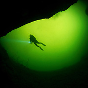 A scuba diver in silhouette exploring the entrance to an underwater cave or blue hole on Eleuthera, Bahamas.