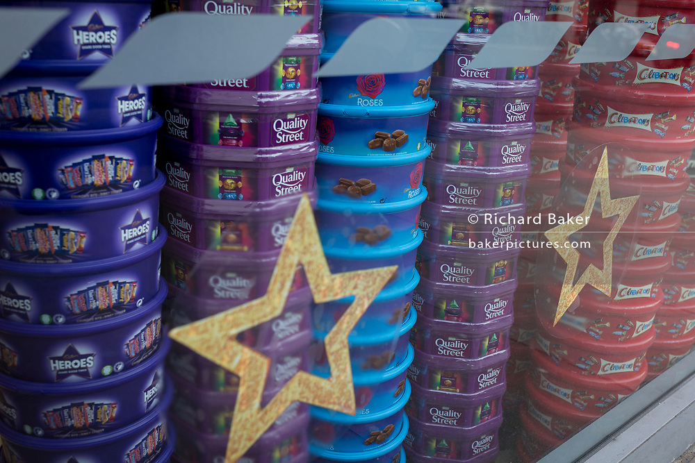 A display of assorted chocolate and sweet boxes of Nestle Quality Street, Cadburys Roses and Heroes plus Mars Celebrations piled up in the Christmas themed window of a local Tescos supermarket, on 20th November 2019, at Smithfield in the City of London, England.