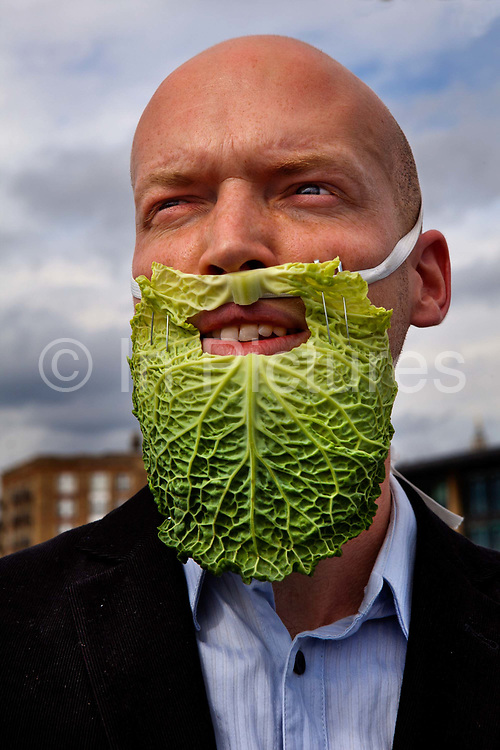Man wearing false beard made from a cabbage leaf, part of the SOIREE theatre group re-enacting some insignificant historical food-related events at the Thames Festival 2011. The Festival celebrates London and the iconic river at its heart - the Thames - by dancing in the streets, feasting on bridges, racing on the river and playing at the water's edge..Southwark Bridge is transformed into a giant banqueting space, designed by Cathy Wren, with visitors invited to share a meal, to eat, drink, dance and make merry..This year, the theme is sustainable fish..