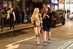 London, January 01 2018. Two women make their way along Brewer Street as revellers in London's West End enjoy New Year's Eve. © SWNS