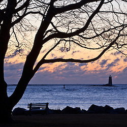 A tree frames Whakleback Light at the mouth of the Piscataqua River as seen from Great Island Common in New Castle, New Hampshire.