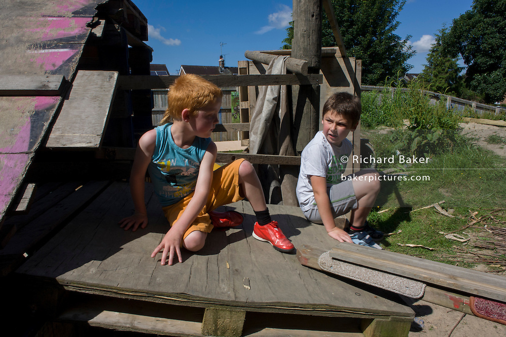 Boys play in risk averse playground called The Land on Plas Madoc Estate, Ruabon, Wrexham, Wales.