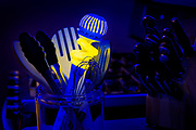 A glass jar holds a glowing molinillo and other kitchen utensils. Blacklight photography.