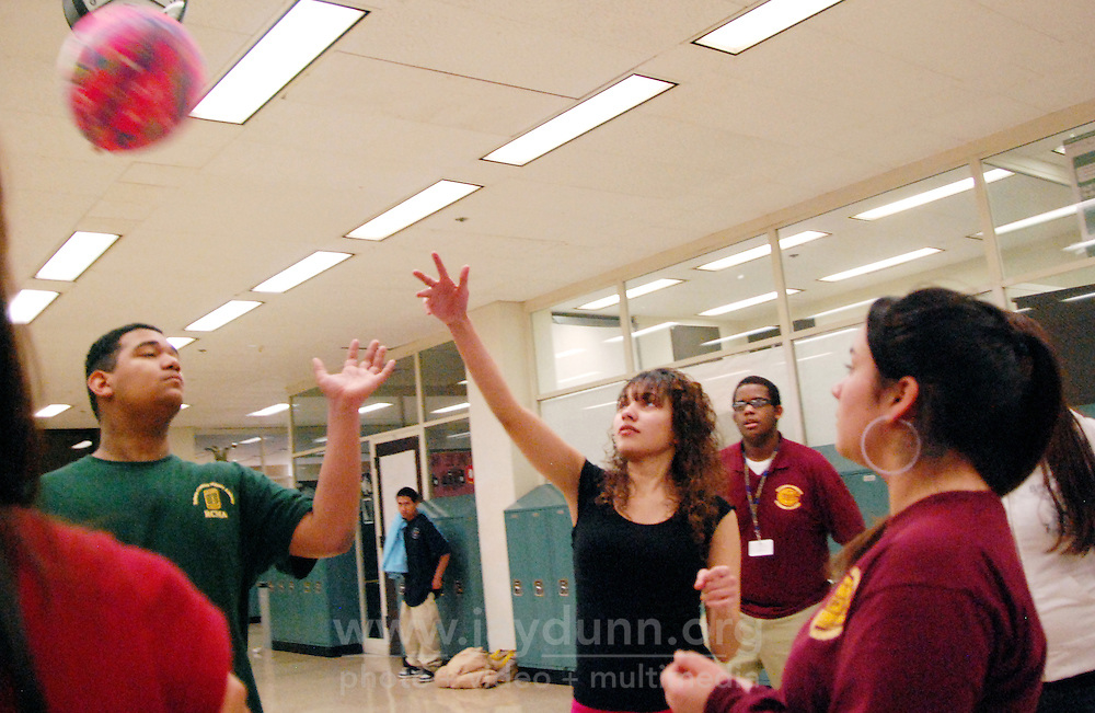 """USA, Chicago, IL, January 19, 2010.  Michael Olmo, Jacqueline Ortiz, Walter Blake, and Atalia Rivera use teamwork to keep the ball off the ground. In its tenth year, the mission of Play for Peace is """"bring together children, youth and organizations from communities in conflict"""" together. The group believes that in cooperative play, laughter is the best medicine, and has proven itself worthy in places as diverse as Guatemala, Northern Ireland, and the Middle East. In practice at Roberto Clemente High School in Chicago's rough-and-tumble Humboldt Park area, students having a Play for Peace """"meeting"""" made remembering people's names' working as a team, encouragement, and partnership a priority in over an hour of flat-out fun. These upbeat, multi-racial students will go on to use their open minds in mentoring younger kids in the spirit of friendship and equality.  Photo for Hoy by Jay Dunn."""