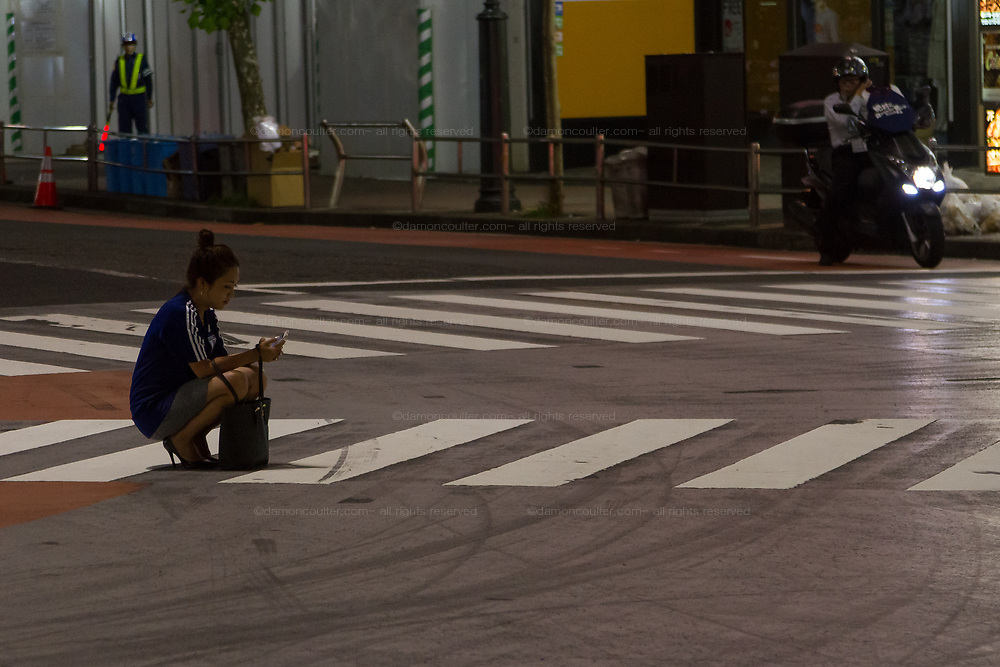 A young Japanese woman, wearing a football top, squats to use a mobile phone in the road in Shibuya after  soccer fans celebrated the Japan National Team qualifying for the next round of the 2018 World Cup in Russia. Japan lost to Poland  0-1 but managed to move to the next stage on points. Thousands of younger fans gathered at Tokyo's iconic Shibuya crossing to enjoy the moment with police controlling the crowds