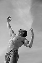shirtless man with arms reaching up to the sky