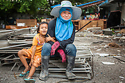 """12 DECEMBER 2012 - BANGKOK, THAILAND:  A demolition worker and her daughter at """"Washington Square"""" a notorious entertainment district off Sukhumvit Soi 22 in Bangkok. Demolition workers on many projects in Thailand live on their job site tearing down the building and recycling what can recycled as they do so until the site is no longer inhabitable. They sleep on the floors in the buildings or sometimes in tents, cooking on gas or charcoal stoves working from morning till dark. Sometimes families live and work together, other times just men. Washington Square was one of Bangkok's oldest red light districts. It was closed early 2012 and is being torn down to make way for redevelopment.    PHOTO BY JACK KURTZ"""