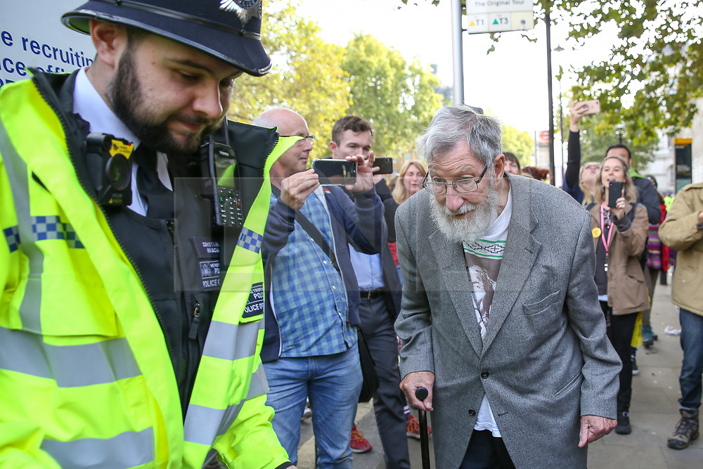 © Licensed to London News Pictures. 09/10/2019. London, UK. Police detain JOHN, aged 91outside Cabinet Office in Westminster on day three of the two weeks protest by environmental and climate change activists. The activists are calling for the government to act on climate change. Photo credit: Dinendra Haria/LNP