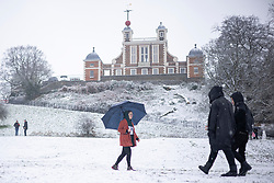 © Licensed to London News Pictures. 24/01/2021. London, UK. People walking past the Observatory in a snow-covered Greenwich Park in southeast London after snow fell over the capital. Photo credit: Rob Pinney/LNP