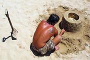 Portuguese Summer. An artist works on a sand sculpture at Praia da Luz beach in Algarve.