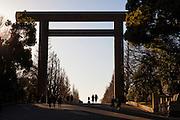 Tokyo-Chiyoda - Two women walk under the great torii - Shrine gate - of the shrine sanctuary Yasukuni jinja.