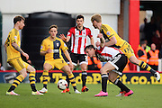 Fulham defender, Tim Ream (13) fouling Brentford attacker, Sergi Canos (47) during the Sky Bet Championship match between Brentford and Fulham at Griffin Park, London, England on 30 April 2016. Photo by Matthew Redman.