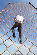 Trainee at US Navy Special Warfare School clubs rope ladder as part of BUDS training.