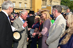 The Prince of Wales (second left) talks with guests during a garden party at Buckingham Palace in London.